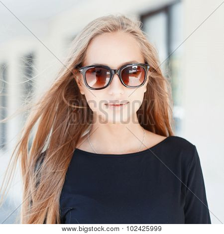 Pretty Woman In Sunglasses On Background Of Windows.on A Sunny Day