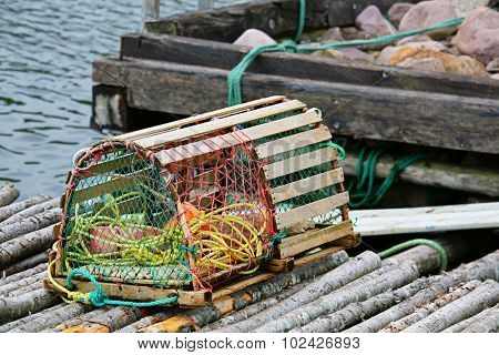 A wooden lobster trap with buoys and rope on a wharf in Newfoundland, Canada.