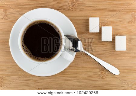 Hot Cup Of Coffee, Spoon And Sugar On Wooden Table