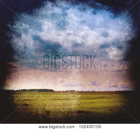 Vintage landscape - cloudy sky and green field