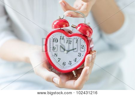 Closeup shot of a woman with white shirt holding red heartshape alarm clock indoor. Female hands holding alarmclock.  Shallow depth of field with focus on the alarm clock.