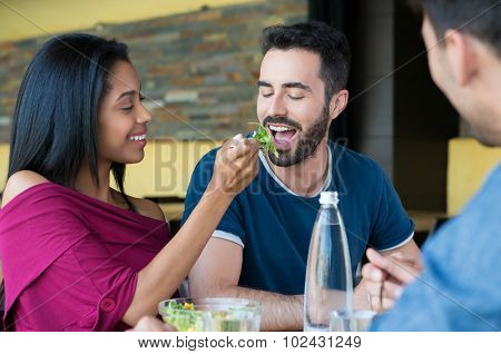 Closeup shot of young woman feeds salad to her boyfriend. Friends having meal together. Happy young friends eating salad at restaurant.