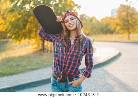 Portrait Of A Pretty Girl With A Skateboard In Her Hand, Outdoors