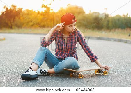 Woman With Skateboard At Sunset.