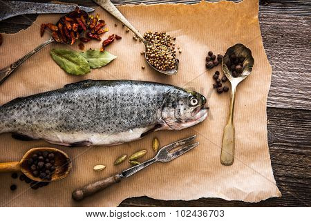 fresh trout with seasonings in a spoons on a table