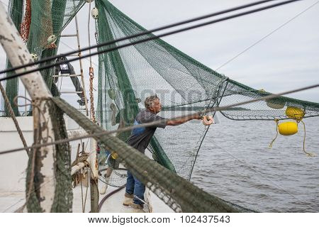 commercial fishermen tending nets on commercial fishing vessel