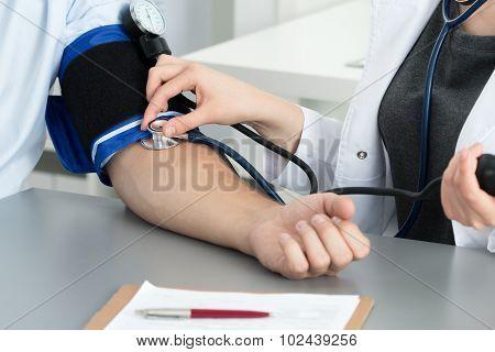 Female Medicine Doctor Measuring Blood Pressure To Her Patient