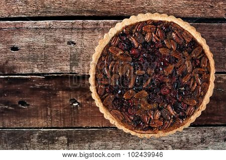 Pecan and cranberry pie on rustic wood background