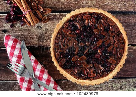 Pecan cranberry pie overhead table scene on rustic wood