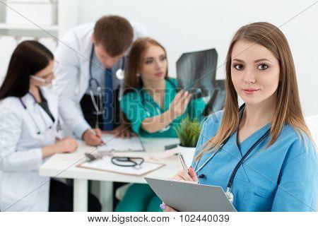 Portrait Of Smiling Female Medicine Doctor Holding Folder With Documents