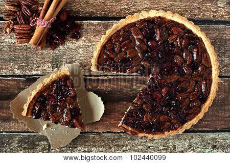 Pecan cranberry pie, overhead rustic table scene with cut slice