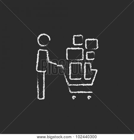 Man pushing shopping cart hand drawn in chalk on a blackboard vector white icon isolated on a black background.