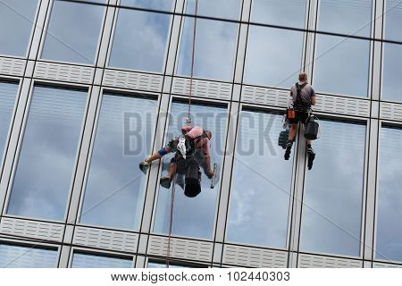 PRAGUE, CZECH REPUBLIC - SEPTEMBER 5, 2015: Two rope access workers clean windows in an office building in Charles Square in Prague, Czech Republic.