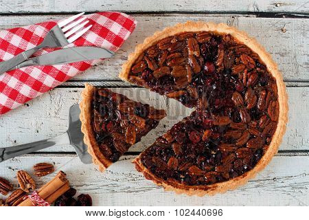 Pecan cranberry pie table scene with slice being removed