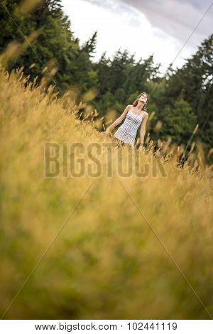 Young Woman Standing In An Autumn Meadow Looking Up In The Sky