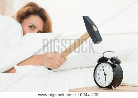 Young Woman Trying To Break The Alarm With Hammer