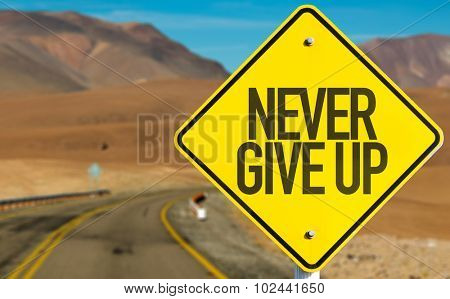 Never Give Up sign on desert road