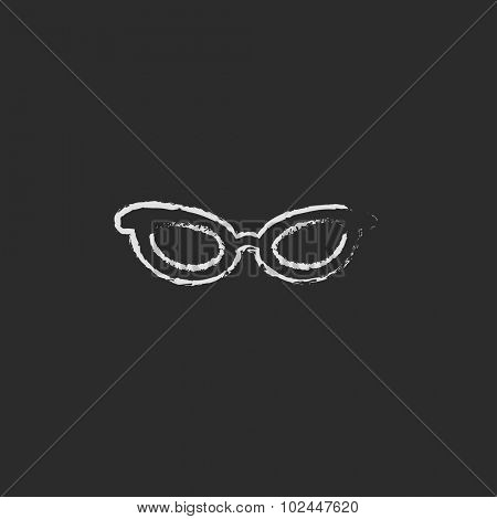 Eyeglasses hand drawn in chalk on a blackboard vector white icon isolated on a black background.
