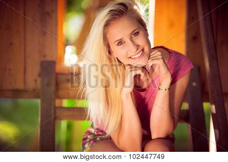 Portrait of a smiling young blonde woman sitting on a banch