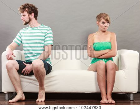 Man And Woman In Disagreement Sitting On Sofa