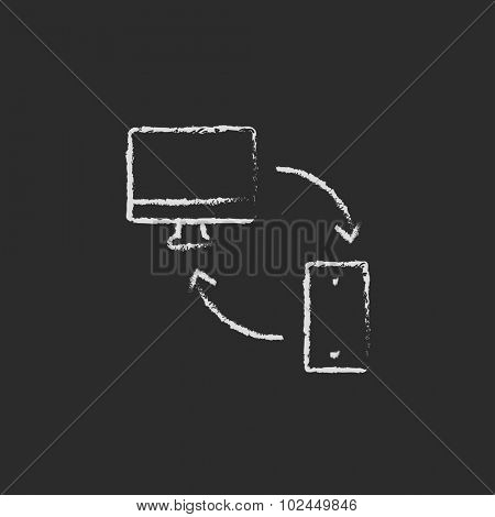 Synchronization computer with mobile device hand drawn in chalk on a blackboard vector white icon isolated on a black background.