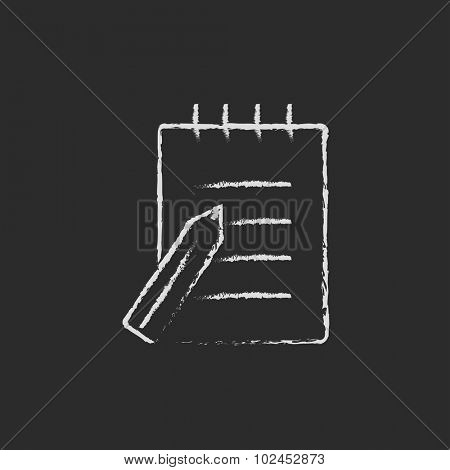 Writing pad and pen hand drawn in chalk on a blackboard vector white icon isolated on a black background.
