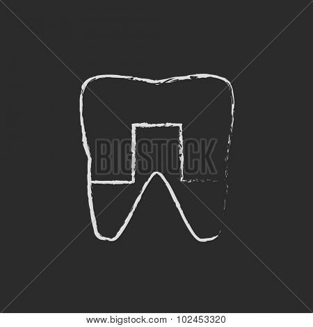 Crowned tooth hand drawn in chalk on a blackboard vector white icon isolated on a black background.
