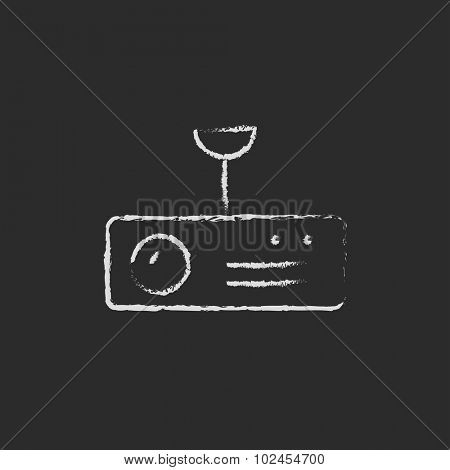 Digital projector hand drawn in chalk on a blackboard vector white icon isolated on a black background.