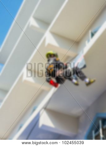 Blurred Firefighters Practice Rappelling On Tower