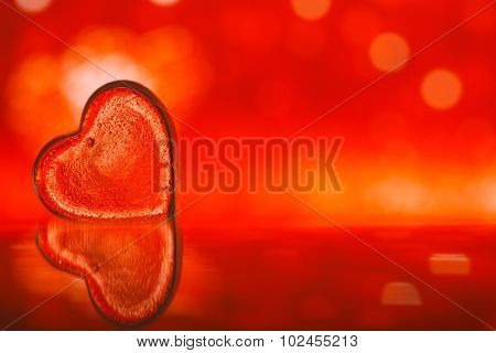 clear glass heart on red  glitter background