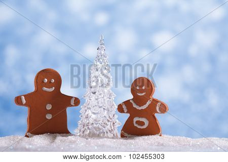 gingerbread boy and girl  with Shinny Glass Christmas Tree, abstract snow blue background