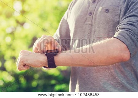 Man Checking His Smartwatch Outside