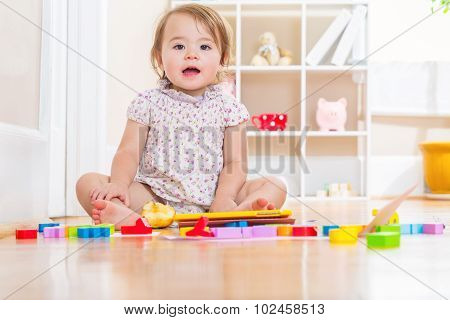 Happy Toddler Smiling And Playing With Toy Blocks