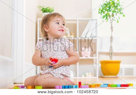 Toddler Girl Smiling And  Playing With Toy Blocks