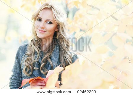 Portrait of young woman in beautiful autumn park