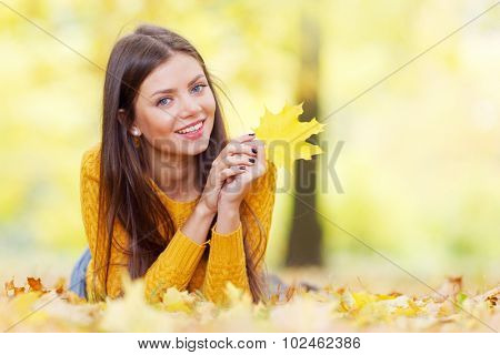 Portrait of a beautiful young brunette woman with autumn maple leaf