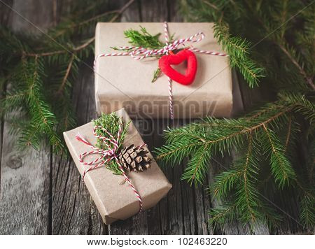 Hand crafted gift on rustic wooden background with with fir branches and cones, toned image