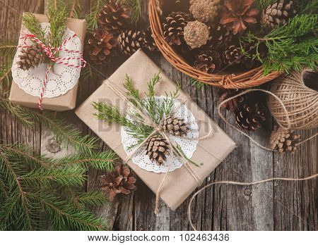 Hand crafted gift on rustic wooden background and a basket with fir branches and cones
