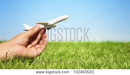 Woman hand holding a model plane with green grass background