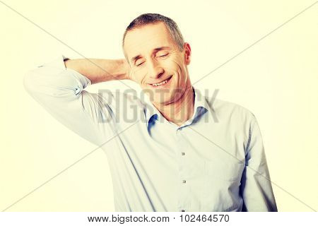 Portrait of a mature man suffering from neck pain.