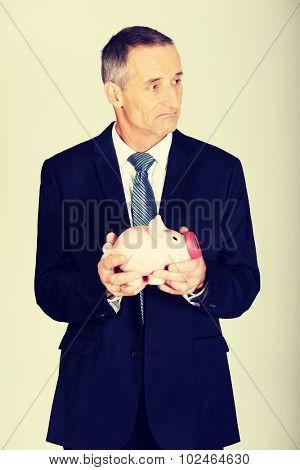 Confused mature businessman holding piggybank.