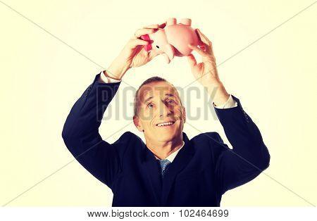 Smiling mature businessman holding piggybank.