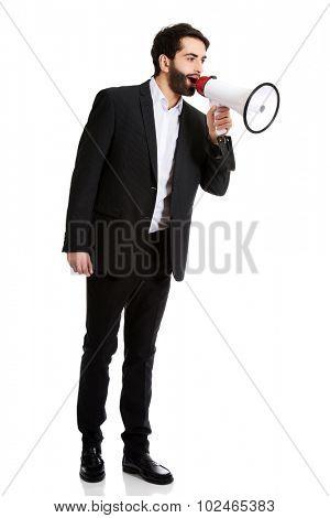 Handsome businessman shouting using a megaphone.