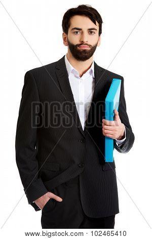 Happy handsome businessman holding a binder.