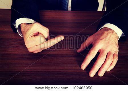 Close up of businessman showing middle finger on the desk.
