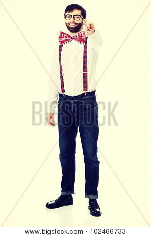 Funny man wearing suspenders pointing on you with big pencil.