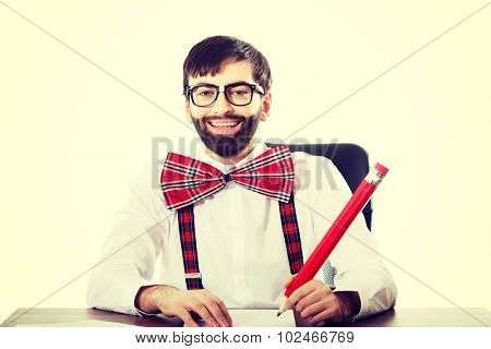 Funny old fashioned man sitting by a desk writing with big pencil.