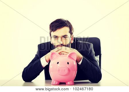 Young businessman with piggybank by a desk.