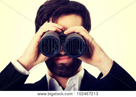 Young handsome businessman looking through binoculars.