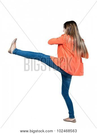 skinny woman funny fights waving his arms and legs. Isolated over white background. Girl in a red jacket raises his right leg high.